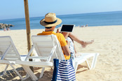 The man looks at his tablet and ignores the beach. Photo by shutterstock